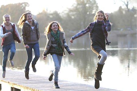 Girls skipping together on lake pier Stock Photo - Premium Royalty-Free, Code: 618-06405866