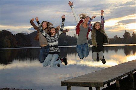 Girls jumping together on lake pier Stock Photo - Premium Royalty-Free, Code: 618-06405870