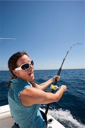 Woman yelling with bent fishing rod on boat. Stock Photo - Premium Royalty-Free, Code: 618-06436518
