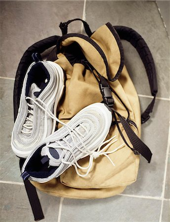 A backpack and gym shoes on a tile floor Stock Photo - Premium Royalty-Free, Code: 618-06504315