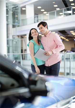 Smiling couple looking at car in car dealership showroom Stock Photo - Premium Royalty-Free, Code: 618-06503953