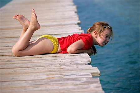 young girl lying on wooden pier Stock Photo - Premium Royalty-Free, Code: 618-06538614