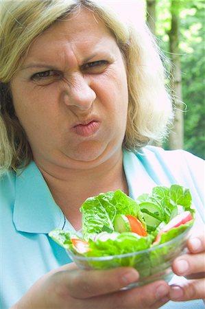 Mature woman grimacing at salad, outdoors Stock Photo - Premium Royalty-Free, Code: 618-06836734