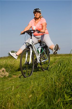 Mature woman cycling through field, smiling Stock Photo - Premium Royalty-Free, Code: 618-06836744