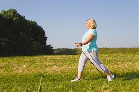 Mature woman hiking through field Stock Photo - Premium Royalty-Free, Code: 618-06836748