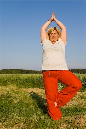 Mature woman performing tree pose in field Stock Photo - Premium Royalty-Free, Code: 618-06836749