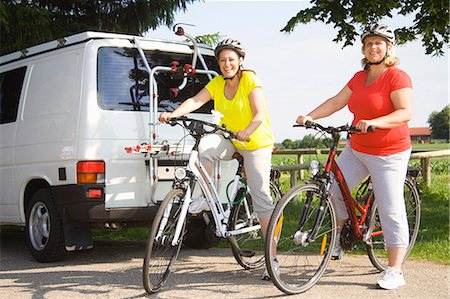 Two friends sitting on bicycles, portrait Stock Photo - Premium Royalty-Free, Code: 618-06836740