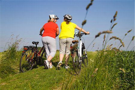 Two friends walking with bicycles through field Stock Photo - Premium Royalty-Free, Code: 618-06836742