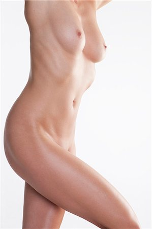 female nude breast sexy - Naked mid adult woman stretching in studio against white background Stock Photo - Premium Royalty-Free, Code: 618-06836784