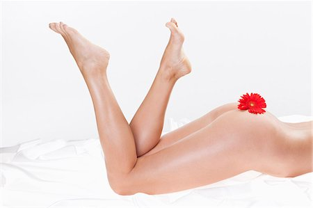 female nud - Low section of naked mid adult woman lying on white sheet with red flower, studio Stock Photo - Premium Royalty-Free, Code: 618-06836793