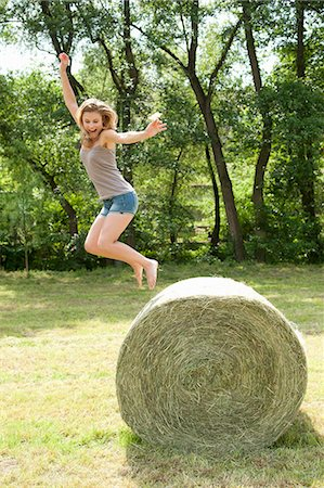 Young woman jumping from hay bale in field Stock Photo - Premium Royalty-Free, Code: 618-06836827