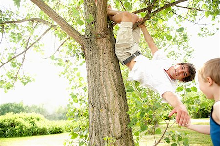 Father climbing tree and reaching for son's hand Stock Photo - Premium Royalty-Free, Code: 618-06836843
