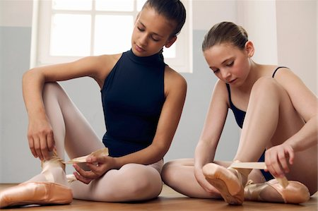 Two female ballet dancers (11-13) on floor, tying up shoes Stock Photo - Premium Royalty-Free, Code: 618-07370199