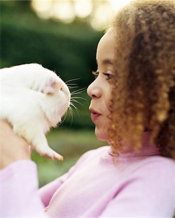 Girl (7-9) holding guinea pig up to face, close-up, side view Stock Photo - Premium Royalty-Free, Code: 618-07372895