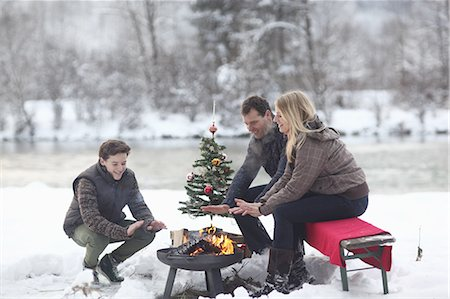 Family sitting at campfire in snow Stock Photo - Premium Royalty-Free, Code: 618-07612099