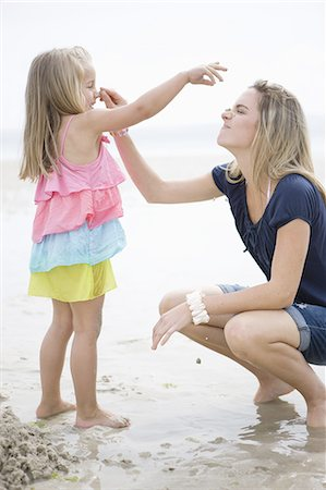 Mother and daughter playing in sand at beach Stock Photo - Premium Royalty-Free, Code: 618-07612117