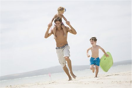 Father and boys running on beach Stock Photo - Premium Royalty-Free, Code: 618-07612144