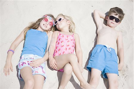 Boy and girls lying together on beach Stock Photo - Premium Royalty-Free, Code: 618-07612146