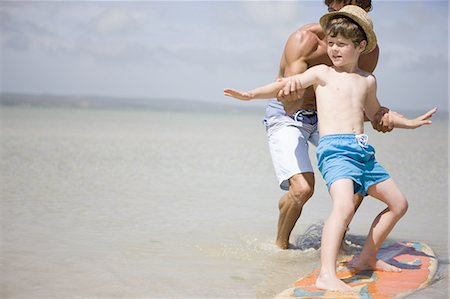 father teaching son how to surf in sea Stock Photo - Premium Royalty-Free, Code: 618-07612155