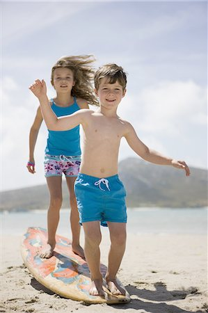Boy and girl balancing on surfboard on beach Stock Photo - Premium Royalty-Free, Code: 618-07612157