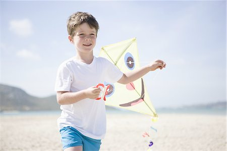 Boy running with kite on beach Stock Photo - Premium Royalty-Free, Code: 618-07612165