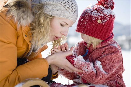 Mother blowing snow from daughters hands Stock Photo - Premium Royalty-Free, Code: 618-07612297