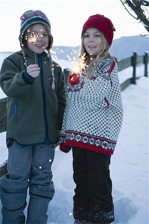 Boy and girl holding sparklers in snow Stock Photo - Premium Royalty-Free, Code: 618-07612327