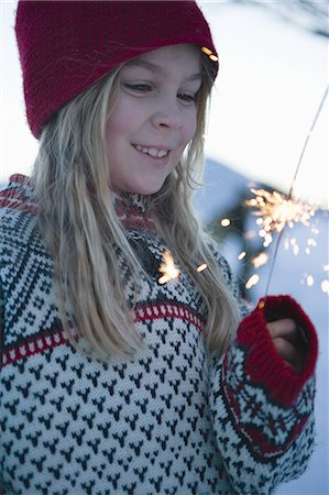 Girl holding sparkler in snow Stock Photo - Premium Royalty-Free, Code: 618-07612329