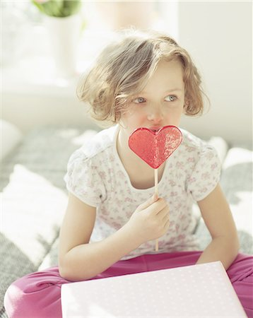 Young girl enjoying heart shaped lolly Stock Photo - Premium Royalty-Free, Code: 618-07612349