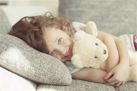 Young girl embracing teddy bear on sofa Stock Photo - Premium Royalty-Free, Code: 618-07612368