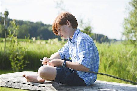 Boy carving wood on riverbank Stock Photo - Premium Royalty-Free, Code: 618-07612469