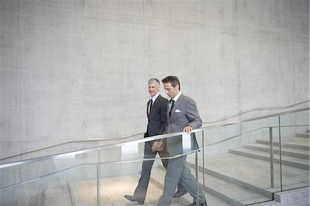 partnership - Businessmen in discussion as they walk down staircase Stock Photo - Premium Royalty-Free, Code: 618-07653695
