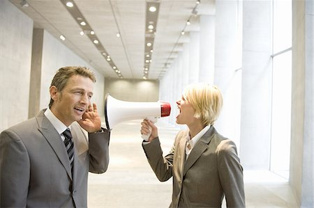 Businesswoman shouting to colleague through bullhorn in lobby Stock Photo - Premium Royalty-Free, Code: 618-07653709