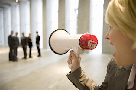 Businesswoman shouting to colleagues through bullhorn in lobby Stock Photo - Premium Royalty-Free, Code: 618-07653710