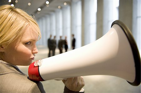 Businesswoman holding bullhorn in lobby of office block Stock Photo - Premium Royalty-Free, Code: 618-07653711
