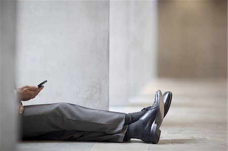 Businessman sitting on floor and using cell phone Stock Photo - Premium Royalty-Free, Code: 618-07653726