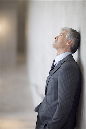 Mature businessman leaning against wall and looking up Stock Photo - Premium Royalty-Free, Code: 618-07653727