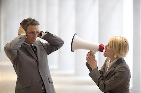 Businesswoman shouting through bullhorn to colleague Stock Photo - Premium Royalty-Free, Code: 618-07653729