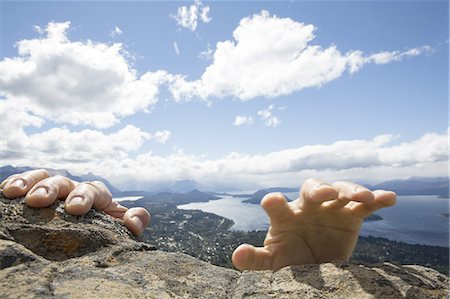 people in argentina - Person's hand grasp summit rocks, lake below Stock Photo - Premium Royalty-Free, Code: 618-07673585