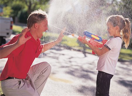 preteen girl wet clothes - daughter shooting water into fathers face with a water gun Stock Photo - Premium Royalty-Free, Code: 618-00445984