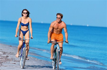 a young couple riding bicycles on the beach Stock Photo - Premium Royalty-Free, Code: 618-00448210