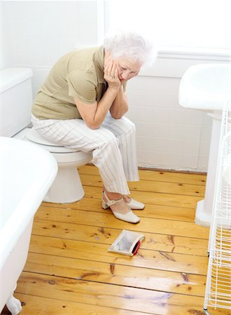 portrait of an elderly woman sitting on a closed commode looking down Stock Photo - Premium Royalty-Free, Code: 618-00464874