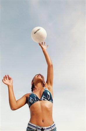 low angle view of a young woman in a bikini top jumping to hit a volley ball Stock Photo - Premium Royalty-Free, Code: 618-00468301