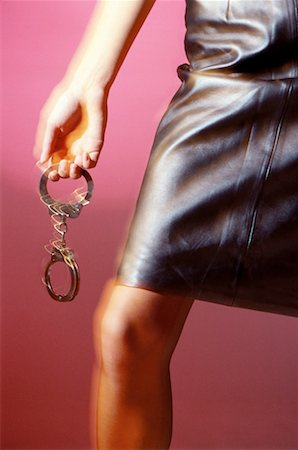 blurred view of woman holding handcuffs Stock Photo - Premium Royalty-Free, Code: 618-00462935