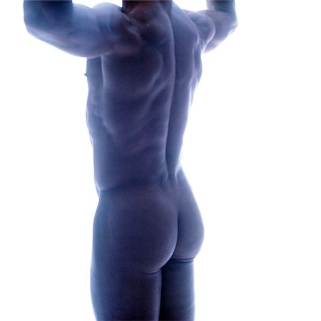 rear view of a nude man standing and flexing his biceps Stock Photo - Premium Royalty-Free, Code: 618-00463247
