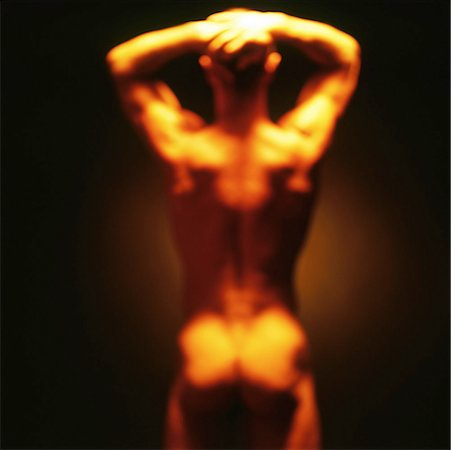 rear view blurred shot of a nude man standing with his hands on his head Stock Photo - Premium Royalty-Free, Code: 618-00463287