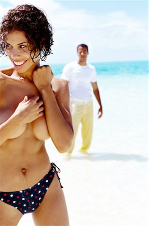 view of a young woman standing topless on the beach with young man in background Stock Photo - Premium Royalty-Free, Code: 618-00463990