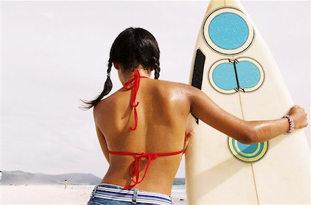 Rear view of a young woman holding a surfboard at the beach Stock Photo - Premium Royalty-Free, Code: 618-00485862
