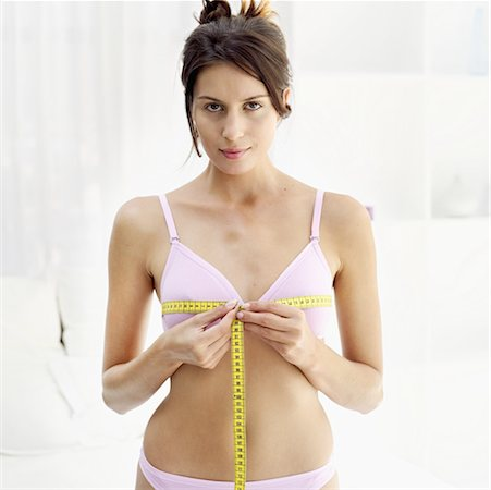 Front view portrait of a young woman measuring her bust with a measuring tape Stock Photo - Premium Royalty-Free, Code: 618-00487272