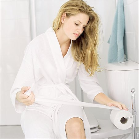 Young woman sitting in a bathroom taking toilet paper from a roll Stock Photo - Premium Royalty-Free, Code: 618-00487348